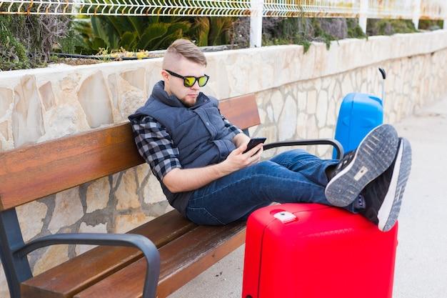 Reise-, tourismus- und menschenkonzept-glücklicher junger mann, der auf einer bank mit zwei fällen sitzt, ist bereit für reisen.