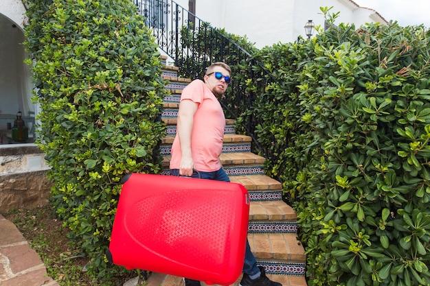 Reise-, tourismus- und personenkonzept - glücklicher mann, der mit rotem koffer die treppe hinaufsteigt und lächelt.