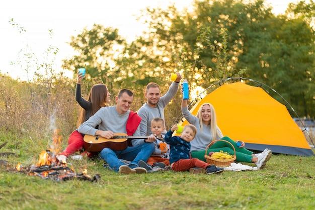 Reise-, tourismus-, wander-, picknick- und personenkonzept - gruppe glücklicher freunde mit zelt und getränken, die auf dem campingplatz gitarre spielen