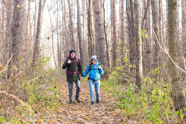 Reise-, tourismus-, wander- und naturkonzept - touristen, die mit einem rucksack in blauen und schwarzen jacken im park spazieren gehen.