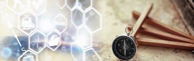 Reise- und abenteuersuchkonzept. vintage gealterte karte mit einem schäbigen buch und einem kompass. schäbiges buch und kompass auf dem tisch.