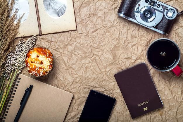 Reise- und gadget-urlaub mit kamera, handy, pass auf braunem papierhintergrund, vintage- und retro-stil
