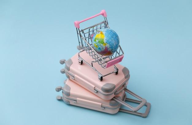 Reise-, urlaubs- oder tourismuskonzept. zwei mini-reisegepäckkoffer und einkaufswagen mit globus auf blau