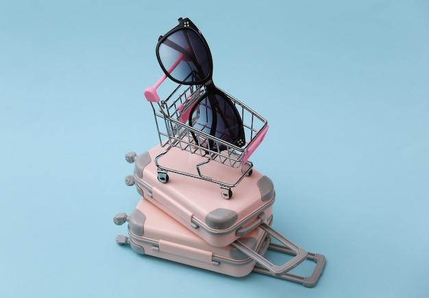 Reise-, urlaubs- oder tourismuskonzept. zwei mini-reisegepäckkoffer und einkaufswagen mit sonnenbrille auf blau