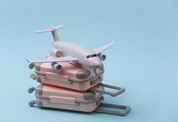Reise-, urlaubs- oder tourismuskonzept. zwei mini-reisegepäckkoffer und flugzeug auf blauem