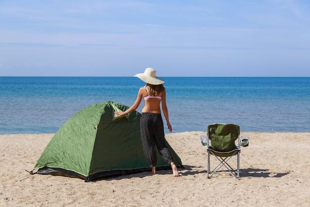 Reise zum meer. camping am strand. urlaub am wasser. männer und ein zelt mit einem touristenstuhl im sand