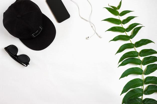 Reiseaccessoires auf weißem hintergrund, intelligente kopfhörerkappe und sonnenbrille aus der sicht von oben