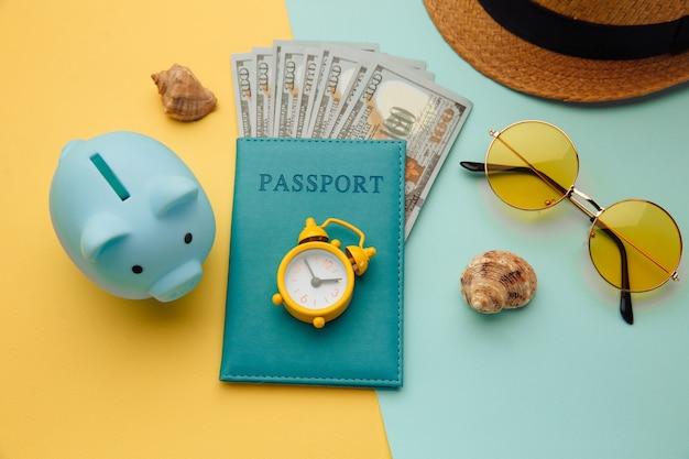 Reiseaccessoires und sparschwein auf blau-gelber oberfläche. sparen sie für unterwegs