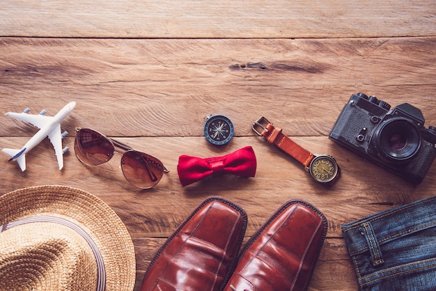 Reisebekleidungszubehör für männer auf holzboden