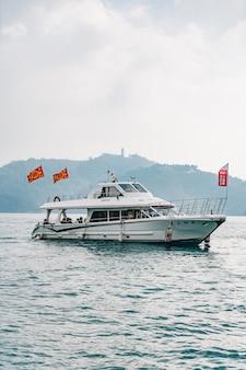 Reiseboote, die über sun moon lake mit berg in yuchi-gemeinde, nantou county, taiwan schwimmen.