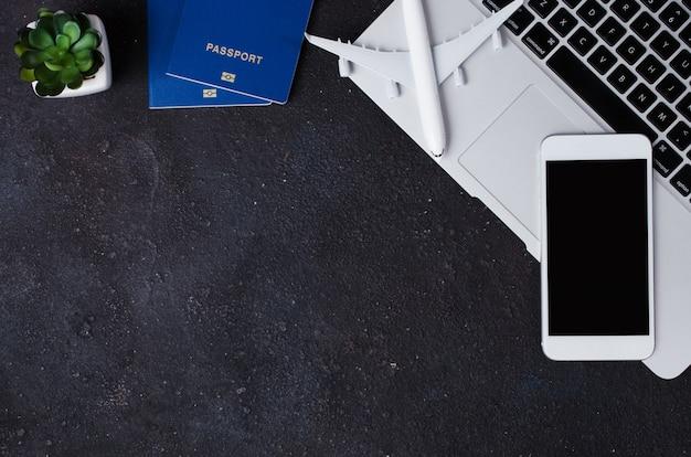 Reisebuchungskonzept. laptop, pässe, smartphone und flugzeugmodell auf dunklem hintergrund.