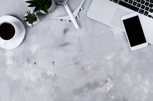 Reisebuchungskonzept. laptop, pässe, smartphone und flugzeugmodell auf grauem beton.