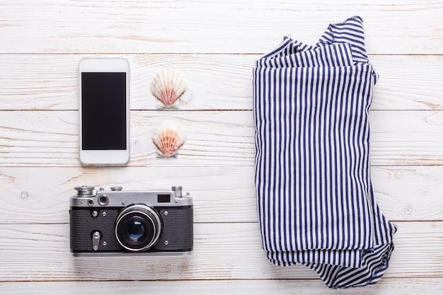 Reiseferienkonzept mit kamera, smartphone, muscheln und gestreiftem t-shirt.