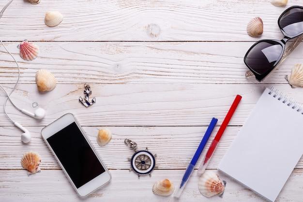 Reiseferienkonzept mit kopfhörern, sonnenbrille, smartphone, muscheln, notizbuch. draufsicht mit kopienraum. flach liegen
