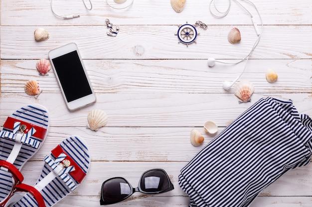 Reiseferienkonzept mit sandalen, kopfhörern, sonnenbrille, smartphone, muscheln und gestreiftem t-shirt.