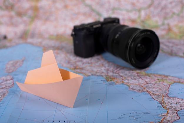 Reiseferienurlaubskonzeptkamera und origami handgemachtes papierschiff papierschiff auf karte nahe italien nah oben
