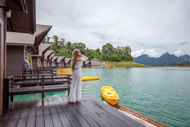 Reisefrau, die auf pier des hölzernen hauses auf see mit tropischen bergen steht