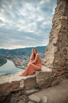 Reisefrau, die gegen den hintergrund der berge und der flüsse aufwirft
