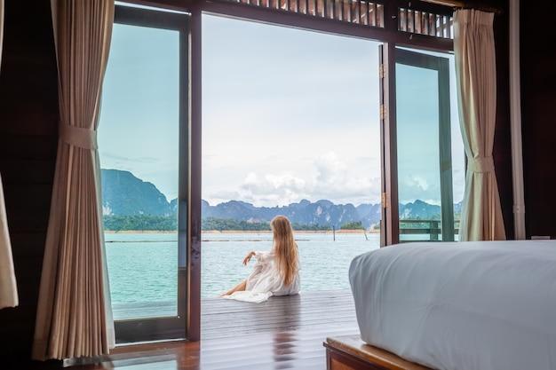 Reisefrau im weißen kleid, das draußen in der nähe des holzhauses auf dem wasser sitzt