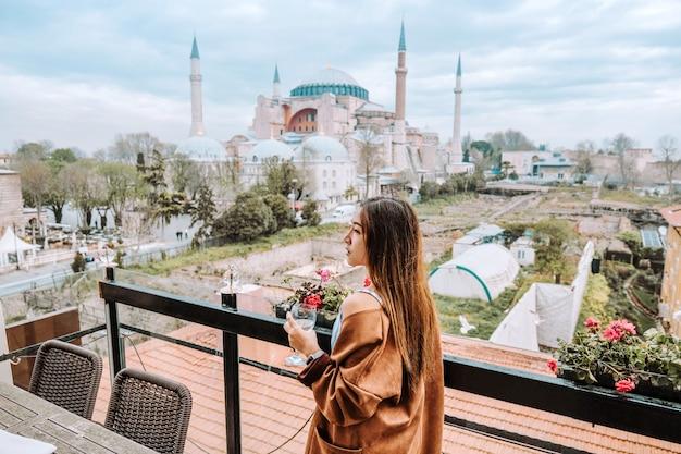 Reisefrau mit türkischem tee mit blick auf die hagia sophia in istanbul, türkei