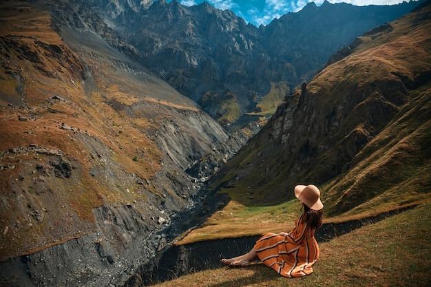Reisefrauentourist, der gegen den hintergrund der berge und des bewölkten himmels aufwirft.