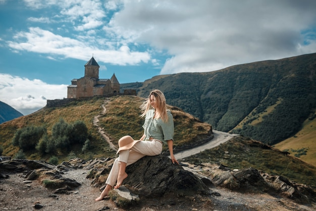 Reisefrauentourist, der gegen den hintergrund der berge und des mittelalterlichen klosters aufwirft.