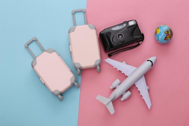 Reisegepäck mit zwei spielzeugen, flugzeug und globus auf rosa blauem pastell. reiseplanung
