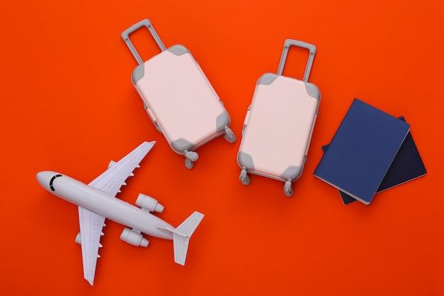 Reisegepäck mit zwei spielzeugen, flugzeug und reisepass auf orange. reiseplanung