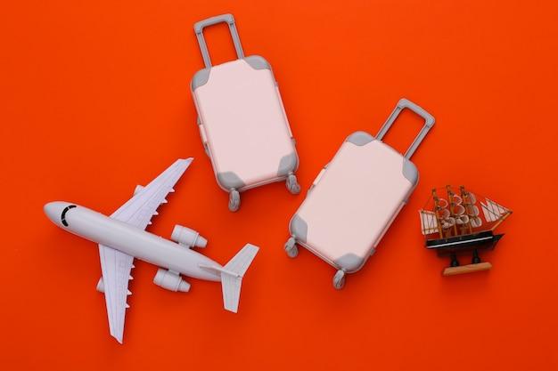Reisegepäck mit zwei spielzeugen, flugzeug und schiff auf orange. reiseplanung