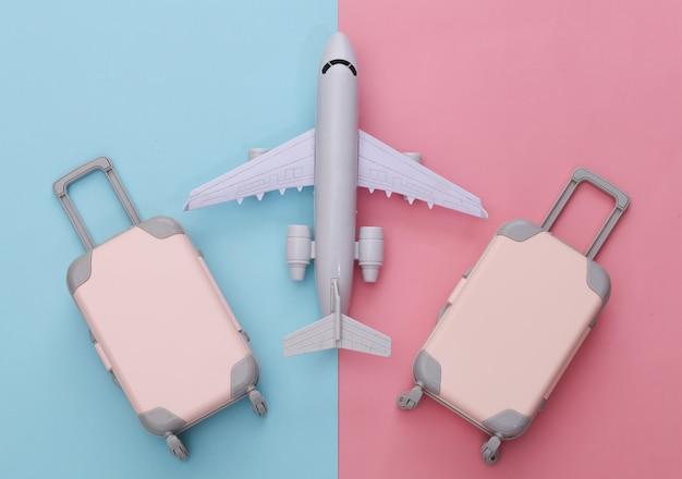 Reisegepäck mit zwei spielzeugen und flugzeug auf rosa blauem pastell. reiseplanung