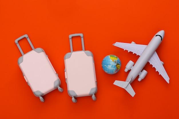 Reisegepäck mit zwei spielzeugen und flugzeug, globus auf orange. reiseplanung