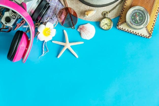 Reisehintergrund von der kamera, vom kopfhörer, von der sonnenbrille, vom kompass, von den starfish und vom oberteil auf blauem hintergrund