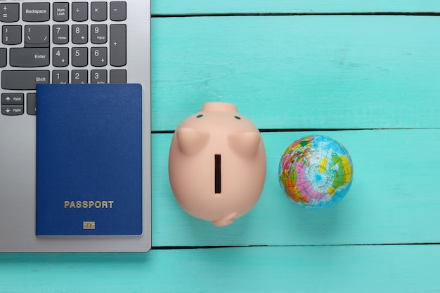 Reiseidee. online-reisen. laptop mit sparschwein, reisepass, globus auf einer blauen holzoberfläche. draufsicht
