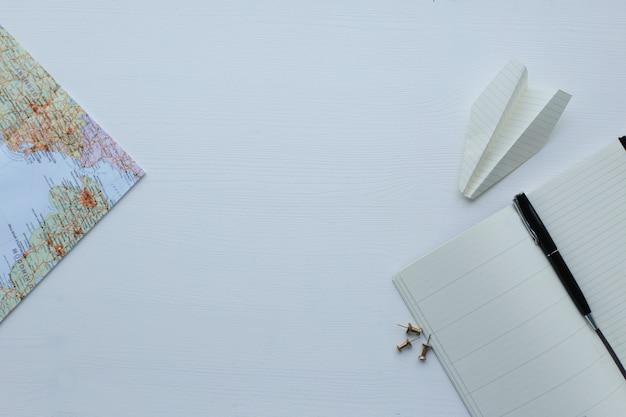 Reisekarte, papierflugzeug und tagebuch