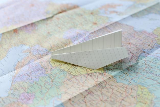 Reisekarte und papierflugzeug