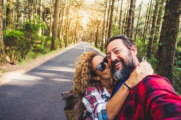 Reisekonzept für menschen im freien mit glücklichem paar kaukasischer mann und frau umarmen und küssen sich mit liebe - beziehung und urlaub im bergwald für fröhliche erwachsene - genuss und glücksleben für