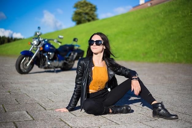 Reisekonzept - glückliche schöne frau, die mit retro-motorrad auf der straße sitzt