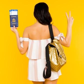 Reisekonzept. junge asiatische frau, die pass mit tickets hält, die mit rucksack zurückstehen, zeigt friedenszeichen auf gelbem raum