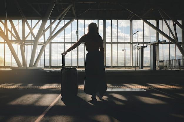 Reisekonzept. junge frau, die mit koffer auf der plattform am bahnhof wartet