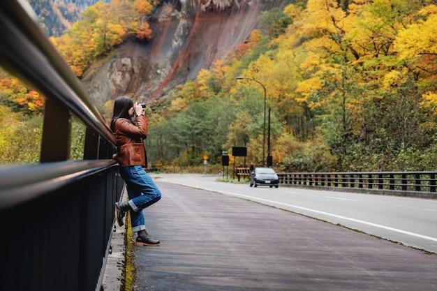 Reisekonzept. junge reisende frau mit der kamera, die foto im fall und im herbst macht