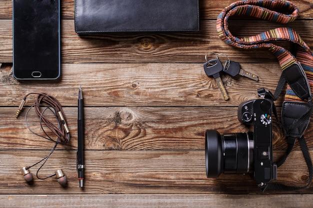 Reisekonzept kopfhörer kamera skizzenbuch geldbörse bleistift und schlüssel auf holzuntergrund