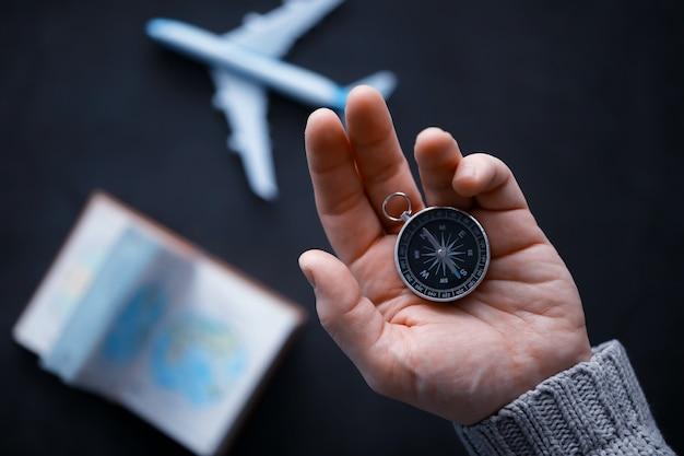 Reisekonzept. magnetkompass in der hand. retro-navigator in der hand eine karte und ein flugzeughintergrund. abenteuer hintergrund.