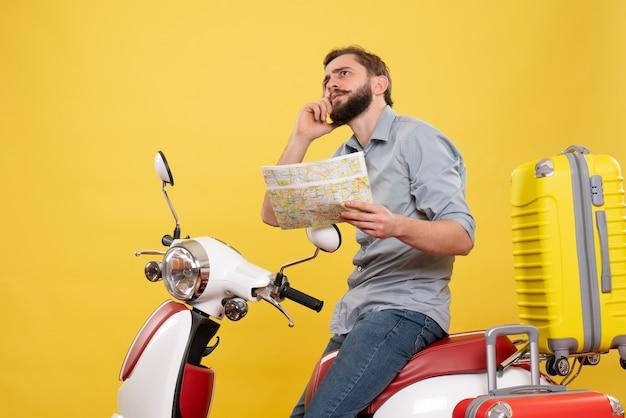 Reisekonzept mit denkendem jungen mann, der auf motorrad mit koffern darauf sitzt und karte auf gelb hält