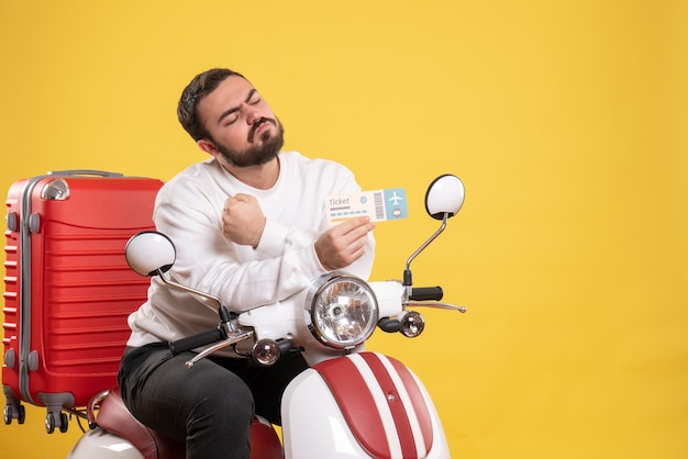 Reisekonzept mit ehrgeizigem mann, der auf einem motorrad mit koffer darauf sitzt und ticket auf gelb zeigt