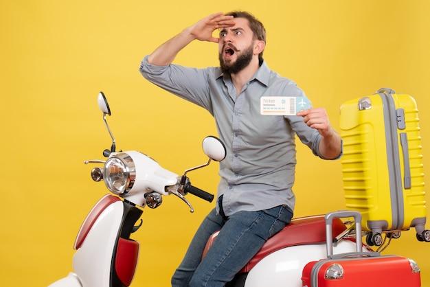 Reisekonzept mit jungem emotional konzentriertem bärtigem mann, der auf motorrad sitzt und ticket auf ihm auf gelb hält