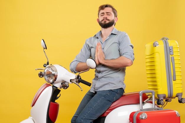 Reisekonzept mit jungem emotionalem bärtigem mann, der auf motorrad auf ihm sitzt und auf gelb träumt