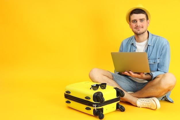 Reisekonzept mit jungem mann auf gelbem hintergrund.