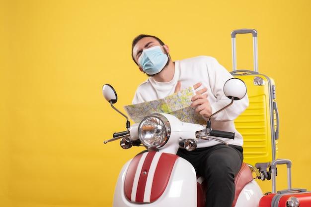 Reisekonzept mit jungem mann in medizinischer maske, der auf einem motorrad mit gelbem koffer sitzt und eine karte hält, die an herzinfarkt leidet