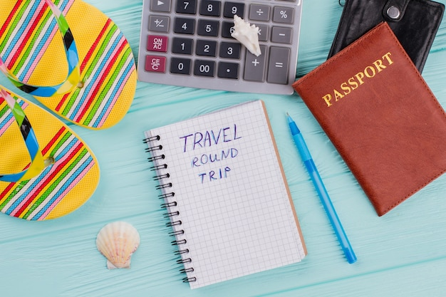 Reisekonzept mit sandalen, reisepass und taschenrechner auf blauem hintergrund. berechnung der flug- und urlaubskosten.