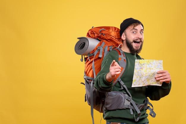 Reisekonzept mit selbstbewusstem jungen mann mit packpack und haltekarte auf gelb
